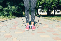 Female legs in sneakers and jump rope outdoors in summer. Sports concept: female legs in sneakers and jump rope outdoors in summer Stock Images