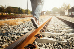 Female legs in sneakers on the rail of the railway. Stock Photo