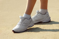 Female legs in sneakers on sand Royalty Free Stock Photo