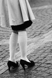 Female legs in socks and black shoes Stock Images