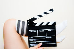 Female legs with socks with movie clapper Stock Photos