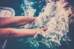 Female legs splashing sea water from a sailing yacht Stock Photo