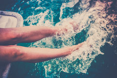 Female legs splashing sea water from a sailing yacht Royalty Free Stock Images