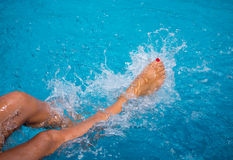 Female legs splashing water at the pool Royalty Free Stock Photos
