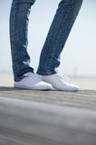 Female legs standing outdoors in comfortable white shoes Royalty Free Stock Images