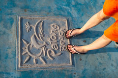 Female legs standing on the plate with the Patong Beach name Stock Images