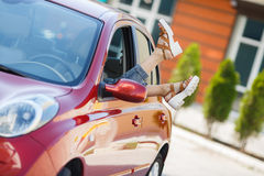 Female legs stick out of a car window. Royalty Free Stock Photo