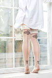 Female legs in stockings near the window Stock Images