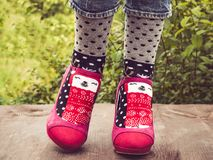 Female legs in stylish, pink shoes and bright socks stock photo