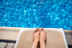 Female legs on a sun lounger on the background of the pool Stock Photos