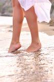 Female legs on sunrise beach. Female legs steps to sea on sunrise beach Royalty Free Stock Photo