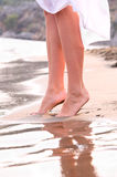 Female legs on sunrise beach. Closeup of female legs on sunrise beach Stock Image