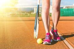 Female legs with tennis racket. Closeup photo of female legs with tennis racket stock image