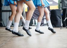 Female legs of three irish dancers. In blue dresses on the stage closeup royalty free stock photography