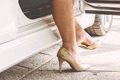 Female legs in tights and high heels in car. Outdoors Stock Photography
