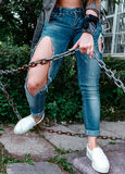 Female legs in torn jeans, close-up, girl holding a rusty chain. Royalty Free Stock Image