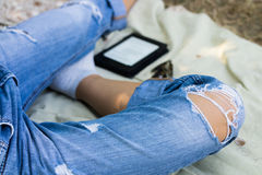 Female legs in torn jeans, electronic book and glasses on the na Royalty Free Stock Photos