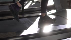 Female legs on treadmill closeup. girl in sneakers on a treadmill. cardio exercises in the gym. Girl running on the treadmill in the fitness room. young woman stock video footage