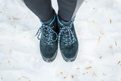 Female legs in trekking sneakers on a background of snow in wint Royalty Free Stock Photography
