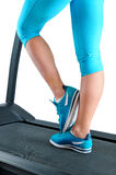 Female legs in turquoise sneakers on a treadmill Stock Photo