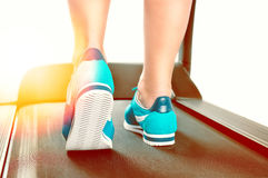 Female legs in turquoise sneakers on a treadmill Stock Image
