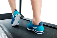 Female legs in turquoise sneakers on a treadmill Stock Images