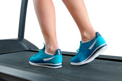 Female legs in turquoise sneakers on a treadmill. Royalty Free Stock Photos