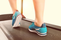 Female legs in turquoise sneakers on a treadmill Royalty Free Stock Photos