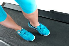Female legs in turquoise sneakers on a treadmill. Royalty Free Stock Photo