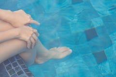Female legs under the swimming pool Stock Photos
