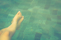 Female legs under the swimming pool Stock Photos