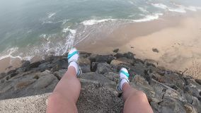 Female legs with a view of the Atlantic Ocean. Empty beach in Povoa de Varzim, Portugal on foggy autumn day with waves. Crashing on shore below and fog in stock footage