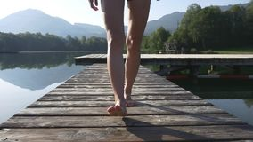 Female legs walk on dock of a mountain lake