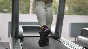 Female legs walking and running on treadmill in gym. Young woman exercising during cardio workout. Feet of girls in Stock Photography