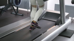 Female legs walking and running on treadmill in gym. Young woman exercising during cardio workout. Feet of girls in. Sport shoes training indoor at sport club stock footage