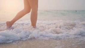 Female legs walking on water waves. Slim female legs move on water at sandy beach.