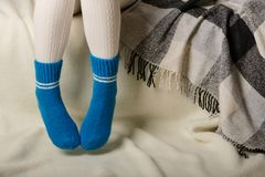 Female legs in warm white knitted tights and blue socks on a white background made of faux fur stock image