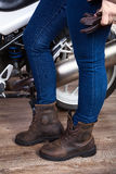 Female legs wearing blue jeans and brown leather safety boots for motorcycling are near motorbike, close up view Stock Photos