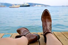Female legs wearing boots by the water Stock Images