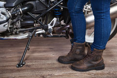 Female legs wearing brown leather safety boots for motorcycling are near motorbike, close up view. Female legs wearing brown leather safety boots for Royalty Free Stock Photo
