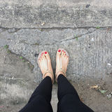 Female Legs Wearing Footwear Shoes or Flip-flop Outdoor Red Nail on Floor Background. Great For Any Use Stock Photos