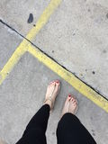 Female Legs Wearing Footwear Shoes or Flip-flop Outdoor Red Nail on Floor Background. Great For Any Use Royalty Free Stock Photography