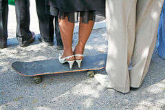Female Legs in white elegant shoes stand on a black skateboard and male legs next Royalty Free Stock Image