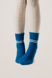 Female legs in white stockings and blue knitted socks. Royalty Free Stock Images