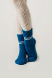 Female legs in white stockings and blue knitted socks. Stock Image