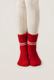 Female legs in white stockings and red knit socks. Stock Image