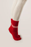 Female legs in white stockings and red knit socks. Stock Photo