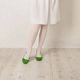 Female legs in white tights, skirt and ballet flats on a white b Royalty Free Stock Photos