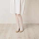 Female legs in white tights, skirt and ballet flats on a white b Stock Photography