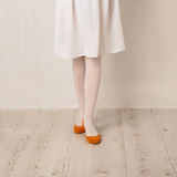 Female legs in white tights, skirt and ballet flats on a white b Stock Images
